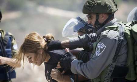 An Israeli border police officer detains a Palestinian woman