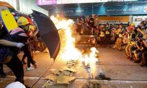 Protesters burn cardboard to form a barrier as they confront with police in Hong Kong., as the Hong Kong protests run into the 5th straight day