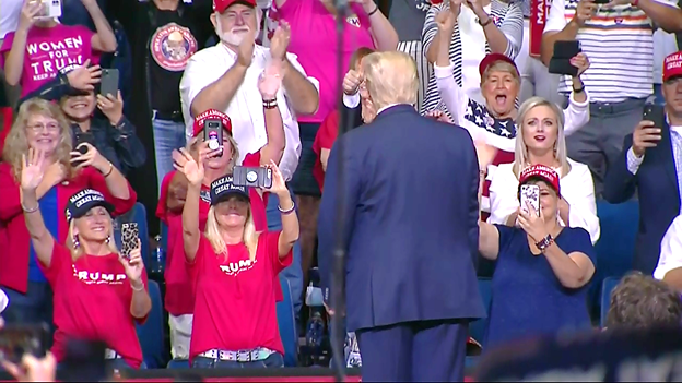 Trump greets supporters as he walks on stage at campaign rally. Most not wearing facemasks