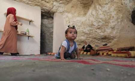 A young baby crawls on the floor in a cave.Palestinian family living in cave home receives demolition notice from Israel