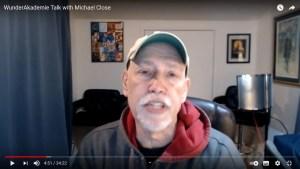 Michael Close sitzt an seinem Schreibtisch; er trägt ein dunkles Sweatshirt und eine weiße Kappe