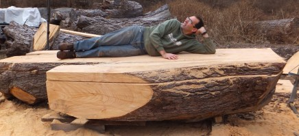Scott Wunder of WunderWoods laying on giant white pine live natural edge milling