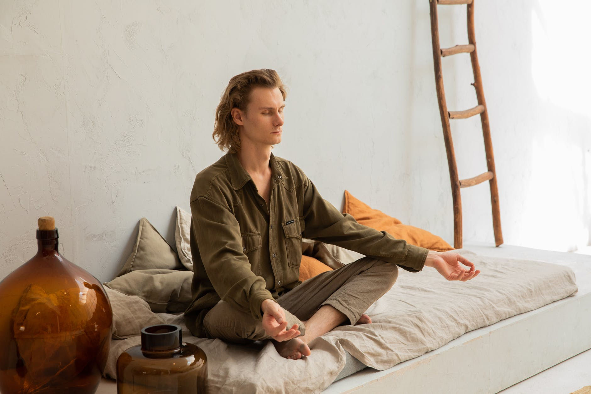 concentrated man meditating in lotus pose on mattress