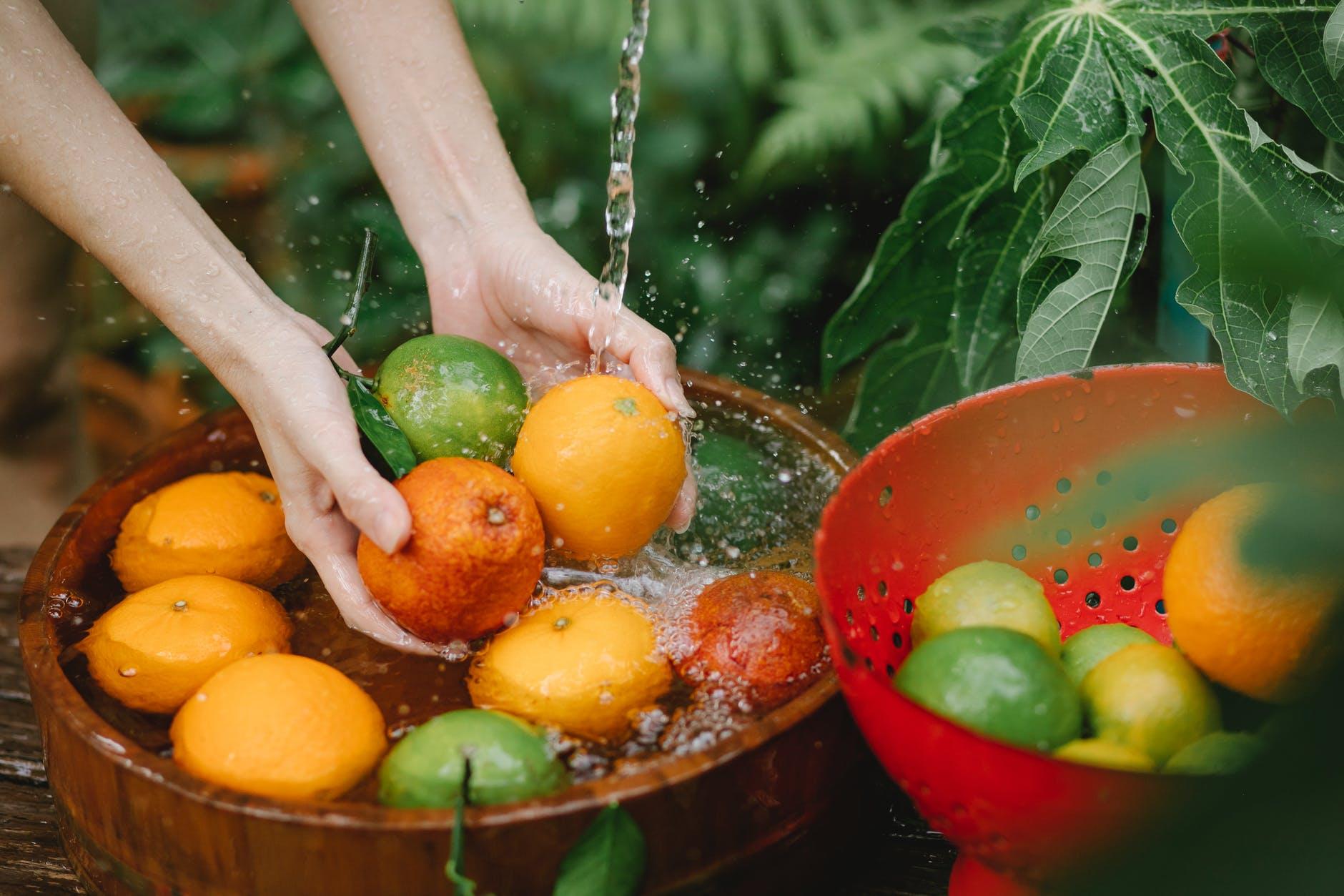 woman washing fresh fruits in tropical orchard