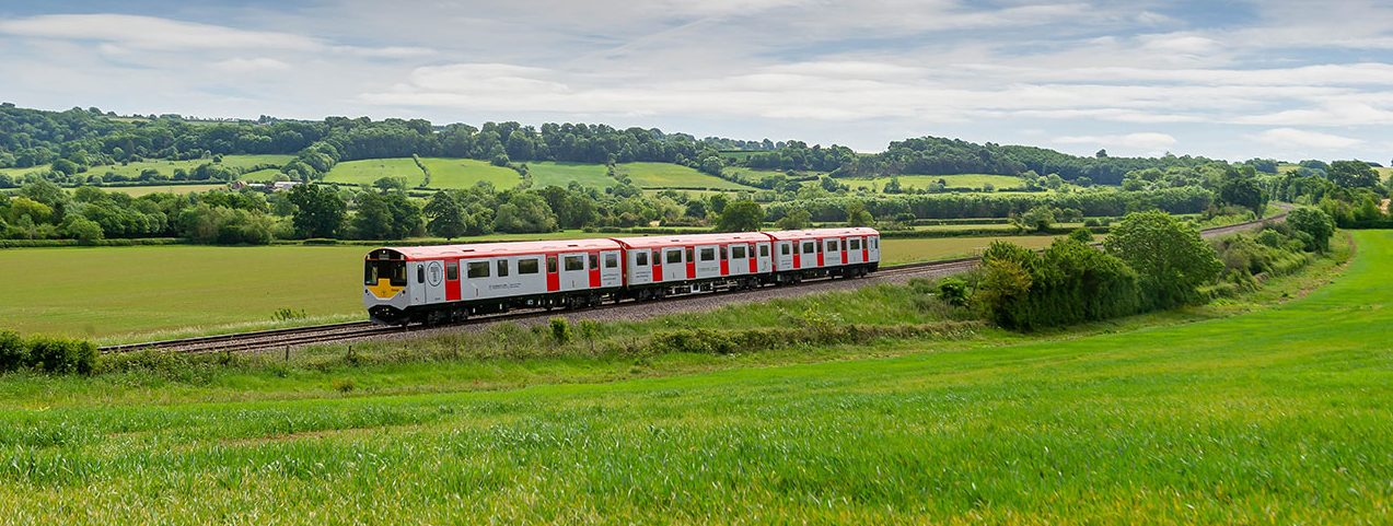 Image of new electric class 230 train travelling through green open countryside. Class 230s are converted from old tube trains so have a more curved outer bodyshell than more conventional rolling stock.