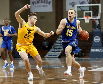 SIOUX FALLS, SD - NOVEMBER 25: Noah Freidel #15 of the South Dakota State Jackrabbits pushes the ball past Sean McNeil #22 of the West Virginia Mountaineers during the Bad Boy Mowers Crossover Classic at the Sanford Pentagon in Sioux Falls, SD. (Photo by Dave Eggen/Inertia)