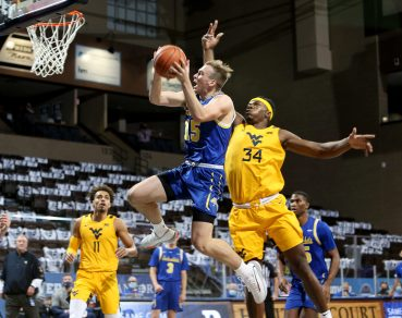 SIOUX FALLS, SD - NOVEMBER 25: Noah Freidel #15 of the South Dakota State Jackrabbits takes the ball to the basket past Oscar Tshiebwe #34 of the West Virginia Mountaineers during the Bad Boy Mowers Crossover Classic at the Sanford Pentagon in Sioux Falls, SD. (Photo by Dave Eggen/Inertia)
