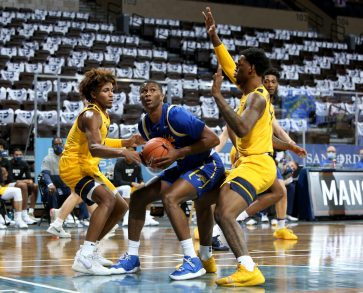 SIOUX FALLS, SD - NOVEMBER 25: Douglas Wilson #35 of the South Dakota State Jackrabbits eyes the basket between Miles McBride #4 and Gabe Osabuohien #3 of the West Virginia Mountaineers during the Bad Boy Mowers Crossover Classic at the Sanford Pentagon in Sioux Falls, SD. (Photo by Dave Eggen/Inertia)