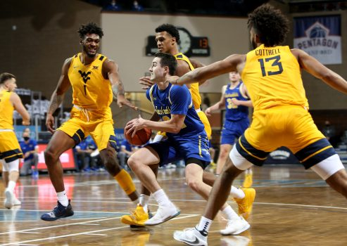 SIOUX FALLS, SD - NOVEMBER 25: Alex Arians #34 of the South Dakota State Jackrabbits drives to the basket between a trio of defenders including Derek Culver #1 and Isaiah Cottrell #13 of the West Virginia Mountaineers during the Bad Boy Mowers Crossover Classic at the Sanford Pentagon in Sioux Falls, SD. (Photo by Dave Eggen/Inertia)