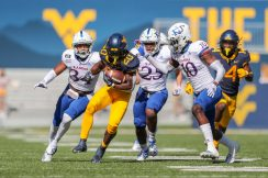 Oct 17, 2020; Morgantown, West Virginia, USA; West Virginia Mountaineers running back Alec Sinkfield (20) returns a punt during the first quarter against the Kansas Jayhawks at Mountaineer Field at Milan Puskar Stadium. Mandatory Credit: Ben Queen-USA TODAY Sports