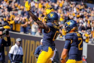Oct 17, 2020; Morgantown, West Virginia, USA; West Virginia Mountaineers wide receiver Bryce Ford-Wheaton (0) celebrates after catching a touchdown pass during the first quarter against the Kansas Jayhawks at Mountaineer Field at Milan Puskar Stadium. Mandatory Credit: Ben Queen-USA TODAY Sports
