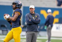 April 24, 2021; Morgantown, West Virginia, USA; West Virginia Mountaineers head coach Neal Brown watches West Virginia Mountaineers wide receiver Sam Brown (17) make a catch prior to the Spring Game at Mountaineer Field at Milan Puskar Stadium. Mandatory Credit: Ben Queen