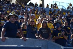 Fans cheer on the Mountaineers with one man wearing a firefighter helmet.