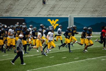 Players jog to warm up positions during a practice in Milan Puskar Stadium on Saturday April 17, 2021. Duncan Slade/WVSN