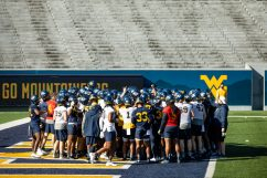 Players huddle during a WVU Football practice on March 27, 2021 in Milan Puskar Stadium. (Duncan Slade/WVSportsNow)