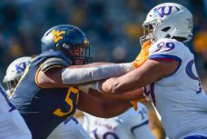 West Virginia Mountaineers offensive lineman Michael Brown (57) blocks Kansas Jayhawks defensive lineman Malcolm Lee (99) Saturday, Oct. 16, 2020, in Morgantown.