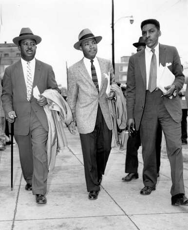 The Rev. Ralph Abernathy, left, Rev. Dr. Martin Luther King, Jr., center, and Bayard Rustin, leaders in the racial bus boycott in Montgomery, Ala., leave the Montgomery County Courthouse on Feb. 24, 1956.  The civil rights leaders were arraigned along with 87 other black activists.  Thousands of supporters walked in protest against the mass indictments and arrests.  (AP Photo) Photo: GENE HERRICK, STF / Beaumont