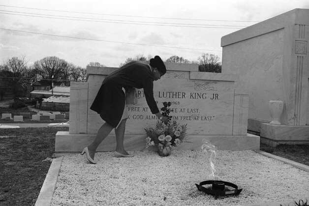 One of the many persons who visit the tomb of Dr. Martin Luther King Jr. daily adds flowers to a vase left by another mourner in Atlanta on April 4, 1969. (AP Photo/BJ) Photo: BJ, STR / Beaumont