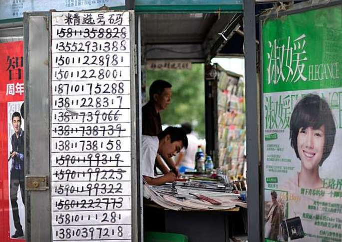 A vendor browses magazine at a news stand with a paper displaying mobile phone numbers for sale in Beijing, Wednesday, Sept. 1, 2010. China began requiring identification on Wednesday from anyone purchasing a new mobile phone number in what it says is a bid to stamp out rampant junk messages but that some say is raising new privacy concerns. Photo: Andy Wong, AP