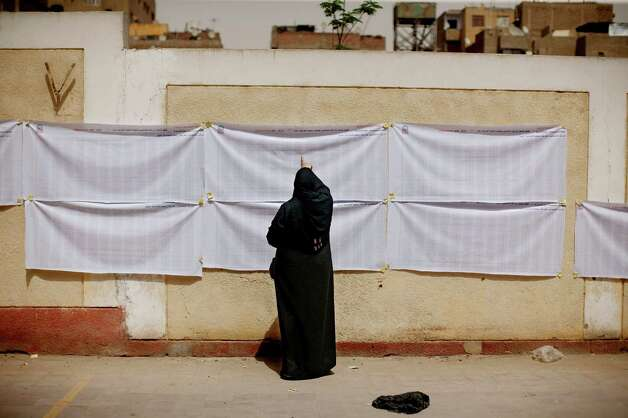 An Egyptian woman searches for her name on a registration list outside a polling station in Helwan, a southern suburb of Cario, Egypt on Wednesday. On Wednesday morning, Egypt commenced two days of presidential voting after 16 months of interim rule by the Supreme Council of Armed Forces. This election is the first free and fair presidential race since the ouster of former President Hosni Mubarak. (AP Photo/Pete Muller) Photo: Pete Muller, Associated Press / AP2012