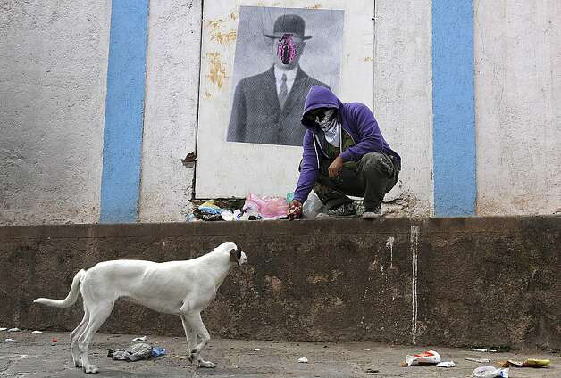 "In this July 29, 2012 photo, a masked artist who calls himself the Urban Maeztro and prefers to remain anonymous for security reasons, stops to play with a street dog after pasting one of his ""interventions"" on a street wall showing Rene Magritte's ""Son of Man,"" substituting the apple covering the face of the suited subject in bowler hat with a pink grenade, in Tegucigalpa, Honduras. The 26-year-old graphic artist left his day job at an advertising agency to work on pieces like this one, to encourage Hondurans think about how violent their country has become.  (AP Photo/Fernando Antonio) Photo: Fernando Antonio, Associated Press / SF"