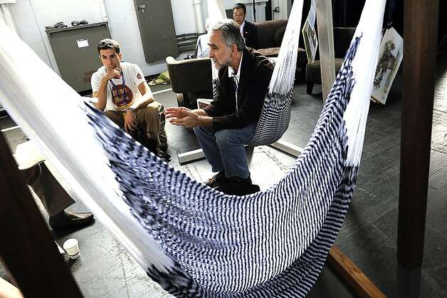 Dan Salcedo (right), CEO of OpenEntry.com, sits in a sustainable hammock made by Yellow Leaf while discussing investment with Yellow Leaf's chief relaxation officer Joe Demin (left) and others at the Socap conference. Photo: Michael Short, Special To The Chronicle