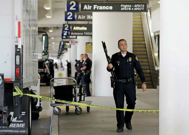 Police stand guard in Terminal 2 at Los Angeles International Airport on Friday, Nov. 1, 2013. A gunman armed with a semi-automatic rifle opened fire at the airport on Friday, killing a Transportation Security Administration employee and wounding two other people. Flights were disrupted nationwide. Photo: Reed Saxon, AP / AP