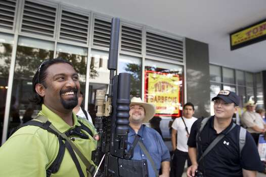 "Bibin Thomas, 27, of Missouri City holds up his AR-15 rifle as he joined a group of about 25 people with the pro-gun rights organization, Come and Take it Houston, as they assembled at City Hall and walked through downtown carrying their guns as part of a rally Thursday, July 4, 2013, in Houston.<br /><br /><br /> ""This is a Come and Take it Houston walk to help inform citizens about the gun laws here in Texas,"" co-organizer Kenneth Lindbloom said. ""In Texas there are no restrictions on the open cary of long arms like rifles and shotguns and we want people to realize that in the hands of good people, guns are not dangerous and they don't kill people. When good people have guns it serves as a deterrent to stop crime.""( Johnny Hanson / Houston Chronicle ) Photo: Houston Chronicle"