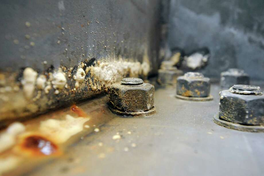 Rust and corrosion from a puddle of water are seen next to bolts in one of the hollow steel box girders that make up the roadway of the Eastern span of the Bay Bridge in Oakland, CA Monday, February 10, 2014. Photo: Michael Short, File Photo / ONLINE_YES