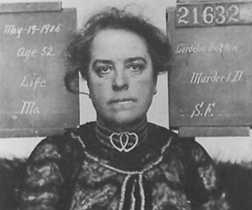 Cordelia's mugshot. She is wearing a lace dress, heart necklace and her hair is messy. She is stony faced.