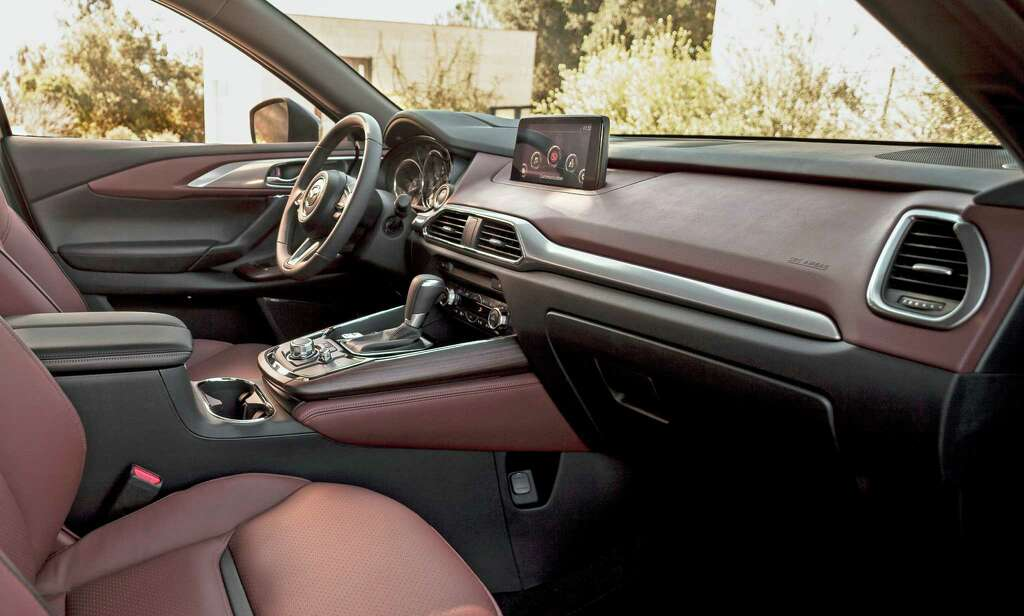 The 2016 Mazda CX-9 Signature model includes such features as auburn-colored Nappa leather seats, rosewood trim from Japanese guitar-maker Fujigen, LED signature accent grille lighting, and LED accent lighting around the automatic shifter. Photo: Mazda / 2015