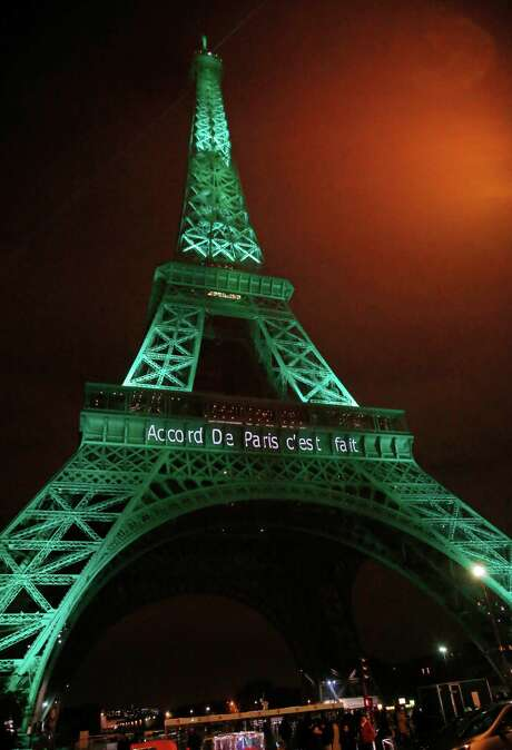 The Eiffel Tower was lit up in green to mark the success of the Paris Agreement on Friday. The pact is intended to help slash man-made global warming gases. Photo: Michel Euler, STF / Copyright 2016 The Associated Press. All rights reserved.