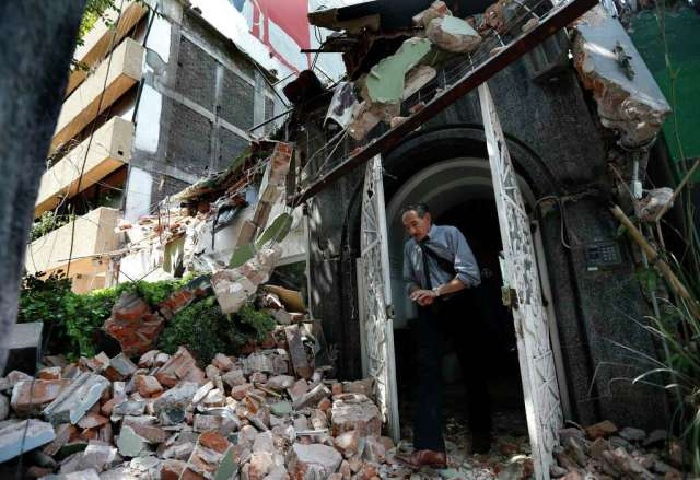 A man walks out of the door frame of a building that collapsed after an earthquake, in the Condesa neighborhood of Mexico City, Tuesday, Sept. 19, 2017. Throughout Mexico City, rescuer workers and residents dug through the rubble of collapsed buildings seeking survivors following a 7.1 magnitude quake. Photo: Marco Ugarte, AP / Copyright 2017 The Associated Press. All rights reserved.