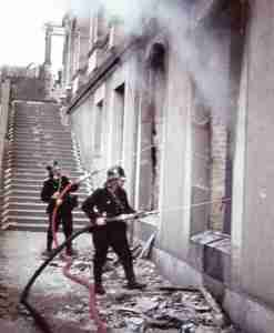 Two firemen fighting a fire after air raid on Kassel.