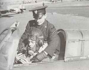 Polish pilot is helped into his plane by a Polish Air Force corporal