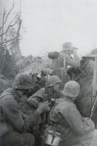 Totenkopf soldiers wait behind an earth wall