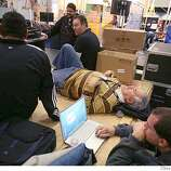 Monte Neece, field marketing manager with Creative Labs, (center lying down) lays down on some boxes while working at the Creative Labs exhibit at the Macworld Conference & Expo which opened on Monday January 14, 2008 in San Francisco, CA. On Tuesday the Expo opens. Neece had hurt his back at CES (Consumer Electronic Show) in Las Vegas held from Jan 7-10 so was resting it. Lea Suzuki/ The Chronicle