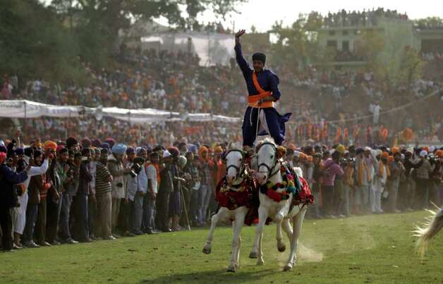"""A Nihang or Sikh warrior, displays his horse riding skills during the annual fair of 'Hola Mohalla' in Anandpur Sahib, in the northern Indian state of Punjab, Friday. Believers from various parts of northern India gather at the religious fair to celebrate the festival of Holi in a tradition set by the tenth Sikh guru Guru Gobind Singh in the seventeenth century. Nihangs or Sikh warriors, display their martial skills and attire during the fair, believed to be maintained in the exact tradition as set by the Guru. Photo: Altaf Qadri, AP / AP"" (photo: seattlepi.com)"