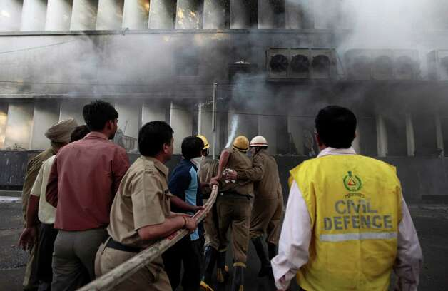 Firefighters spray water, after a fire broke out in a multi-story building housing the Punjab National Bank on Parliament Street in New Delhi, India, Wednesday. No casualties have been reported. Some of the injured, who had trouble breathing, were taken to hospitals according to local news reports. (AP Photo/Saurabh Das) Photo: Associated Press / SL