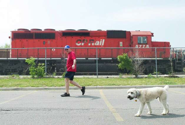 A man walks his dog in a parking lot next to CP Rail trains which are parked on the train tracks in Toronto on Wednesday. Canada's labor minister said Wednesday the government will introduce legislation if necessary to end a strike at Canadian Pacific railway, which has forced the suspension of its freight service in Canada and the United States. (AP Photo/The Canadian Press, Nathan Denette) Photo: Associated Press / SL