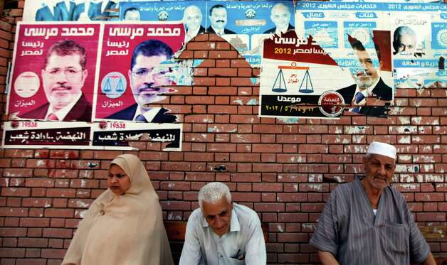Egyptians sit beneath campaign posters supporting the Muslim Brotherhood's presidential candidate Mohammed Morsi outside a polling center as they wait to cast their votes in Alexandria, Egypt, Wednesday. More than 15 months after autocratic leader Hosni Mubarak's ouster, Egyptians streamed to polling stations Wednesday to freely choose a president for the first time in generations. Waiting hours in line, some debated to the last minute over their vote in a historic election pitting old regime figures against ascending Islamists.(AP Photo/Khalil Hamra) Photo: Khalil Hamra, Associated Press / AP