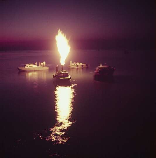 Oil workers fishing trout by light of oil flare at Shamrock Cove in the Gulf of Mexico in 1954.