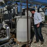 Aaron Mandell, Co-founder and Chairman of WaterFX, peers into a collection barrel full of clean water at the WaterFX desalination plant pilot project in Fresno County near the Panoche Water and Drainage District headquarters in Firebaugh, Calif. The demonstration plant uses solar troughs and Concentrated Solar Still technology to desalinate waste water provided by the Panoche Water and Drainage District. Mandell hopes to eventually build a plant that can process 2 million gallons of water a day, water that is sorely needed in the valley.