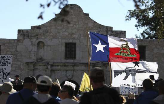 Flags fly at the Come And Take It San Antonio pro-gun rally on Saturday, Oct. 19, 2013. Several hundred pro-gun owners displayed their rifles and long arms at a rally on the grounds of the Alamo. The group later marched to Travis Park where the event concluded. (Kin Man Hui/San Antonio Express-News) Photo: San Antonio Express-News