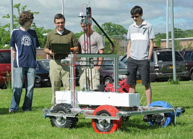 From left, college mentor Ryan MacKenzie, volunteer Navy veteran Robert Svec, and students John DerBoghossian and Ethan Kranick watch the sample return robot move on the grass at Schenectady High School Friday, June 6, 2014 in Schenectady, N.Y. The Schenectady High School science team named the Retrievers is competing in the NASA Sample Return Robot Centennial Challenge. The robot moves using software on the computer held by Svec. (Lori Van Buren / Times Union) Photo: Lori Van Buren / 00027231A