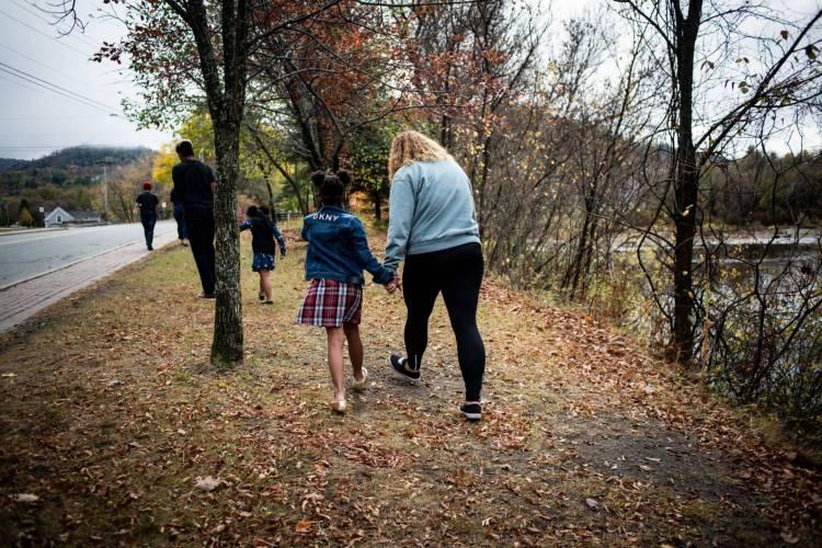 Parent walks with child alongside river