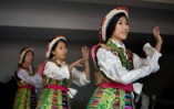 Youngsters in traditional costumes practice a dance they will perform for the Dalai Lama.