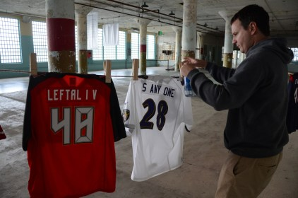 "Artist Nelson Saiers adjusts one of the jerseys in his exhibit, ""Shortening: Making the Irrational Rational"" on Tuesday, October 25, 2016. He conceived the idea for the piece after a friend told him about the toll long prison sentences -- or ""football numbers"" -- were taking on communities."