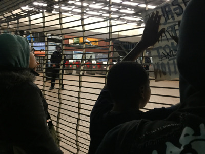 Protesters shake gates blocking the entrance to the West Oakland BART Station as police watch. (Alex Emslie/KQED)