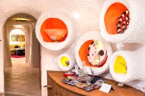 Amorphic shaped alcoves dotting the walls of the kitchen hold small art sculptures.